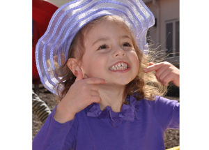 Elementary Gallery student smiling with a silly hat on